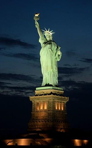Bateaux New York dîner-croisière sur le pont du bâteau vue sur la Statue de la Liberté à la tombée de la nuit