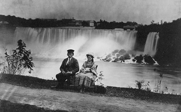 Young man and girl seated on the Canadian side of Niagara Falls