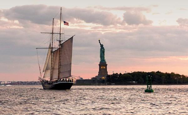 Goélette approchant la Statue de la Liberté au coucher du soleil