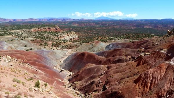 Les contreforts des Circle Cliffs, en arrière plan les paysages rouges et verdoyants de Capitol Reef National Park, au loin vers l'infini les Henry Mountains.